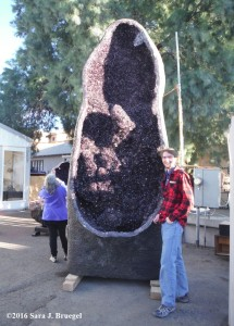 A large geode with a slightly taller than average man.  Photo copyright Sara J. Bruegel, 2016